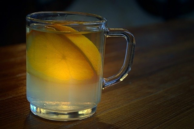 Glas of hot spiced wine with a piece of lemon in it on a table