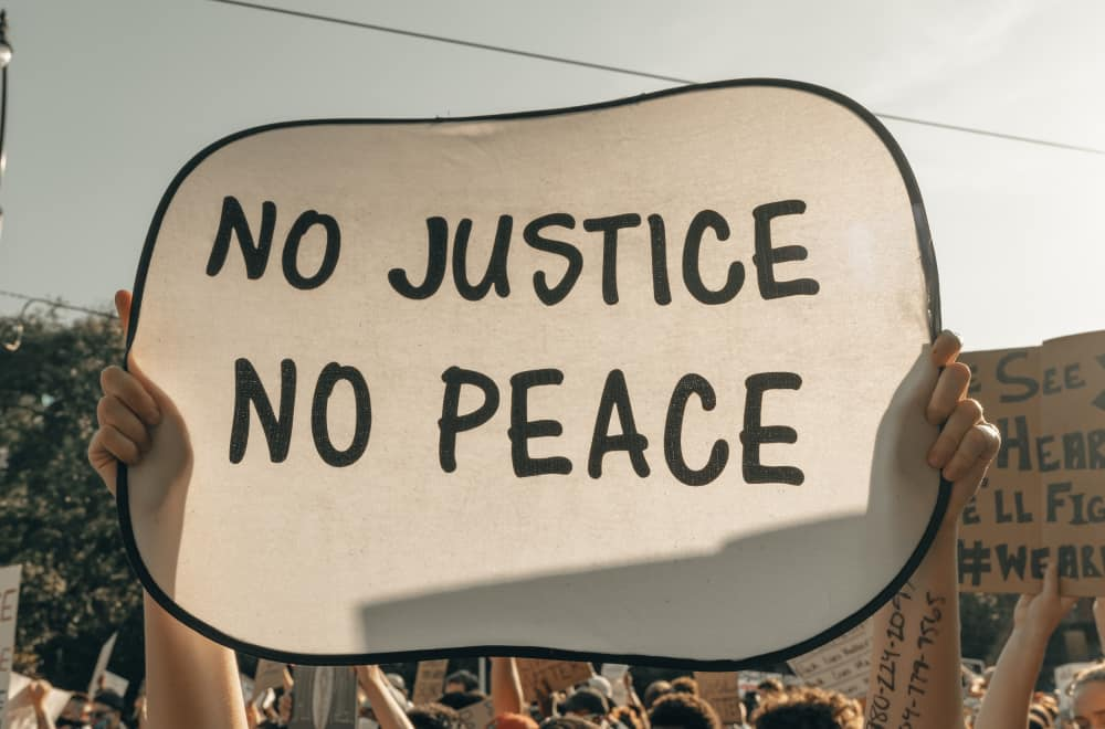 No Peace - no Justice - Woman on protest with banner